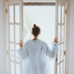 Frau an offenem Fenster, Lüften gegen Schimmelpilze