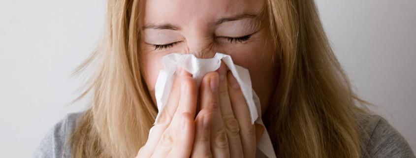 Frau niesst wegen Schimmelpilzen